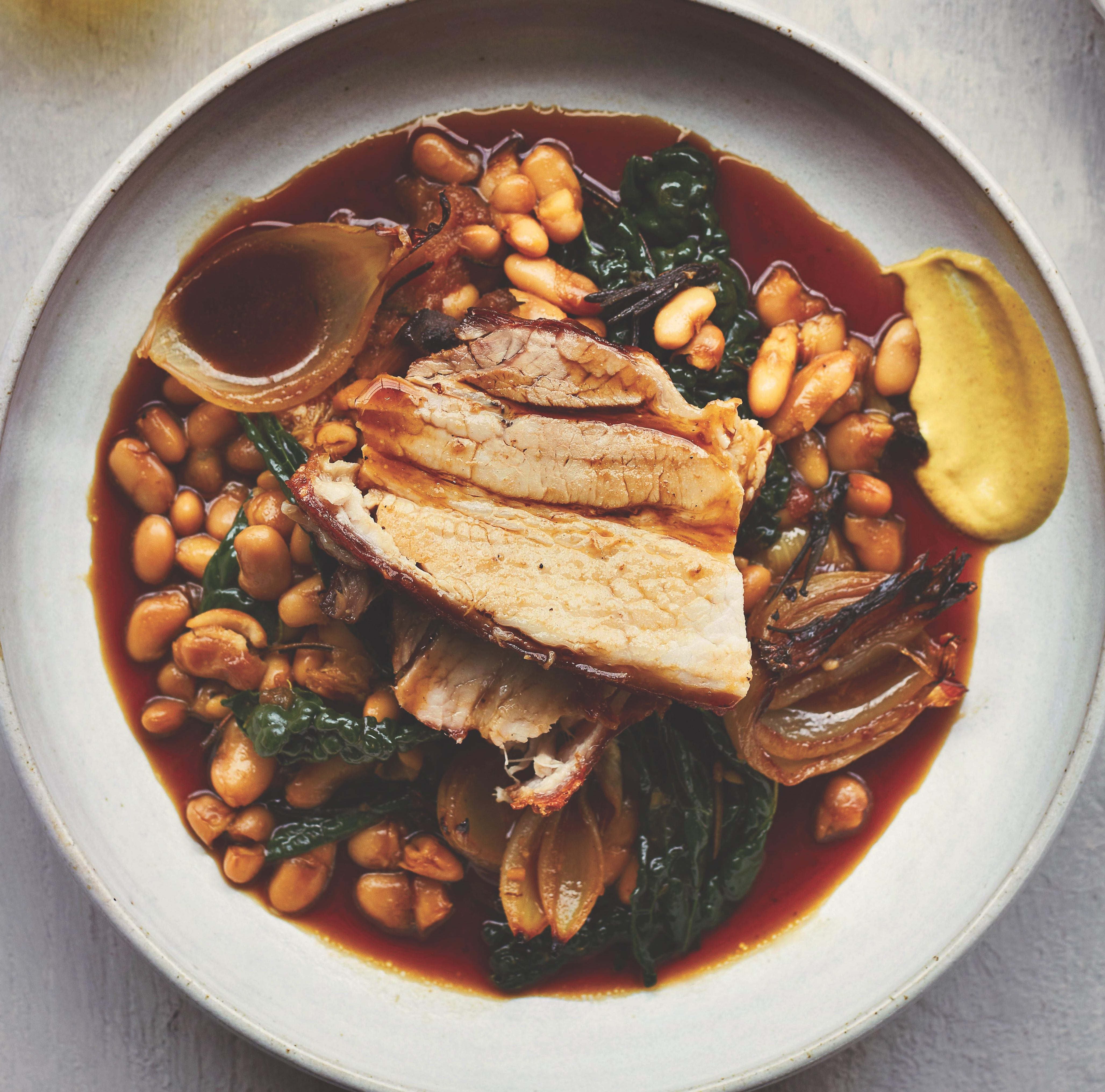 Slow-roasted pork belly with cannellini beans recipe